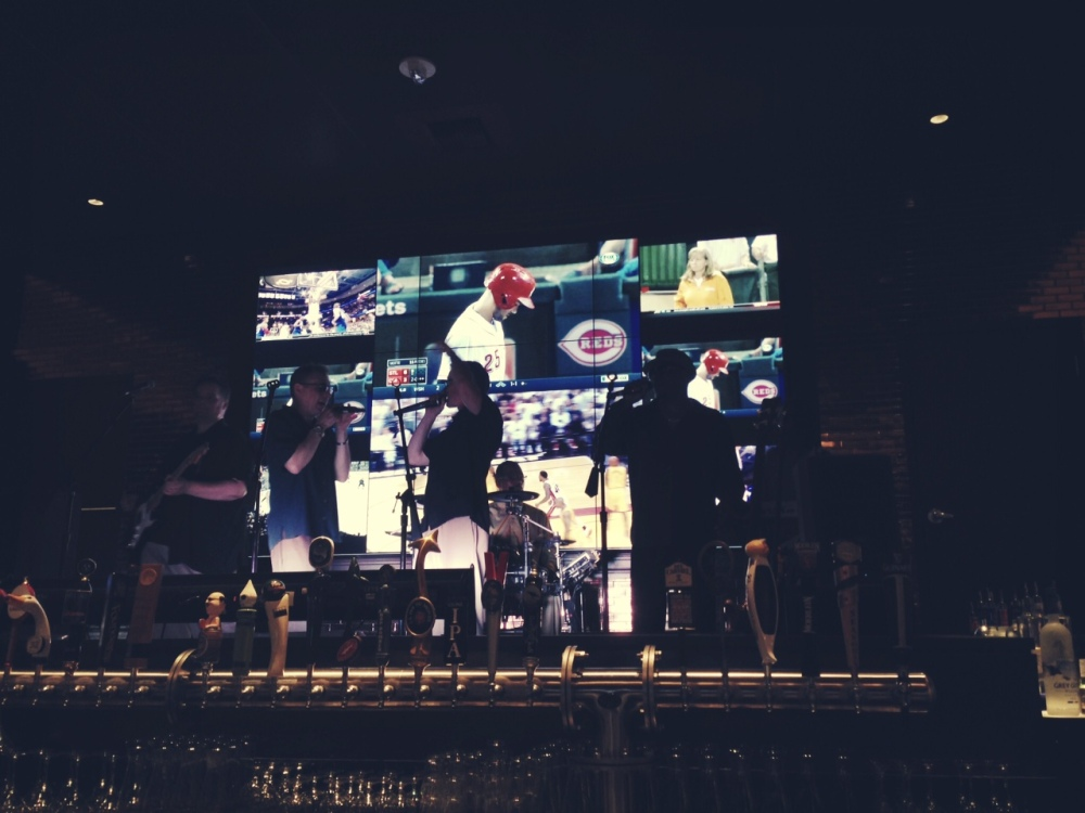 Band playing on a stage at the bar with the Reds game playing on multiple screens in the background.